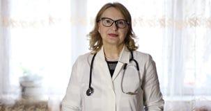 Retrato de un viejo doctor de sexo femenino en vidrios con un estetoscopio almacen de video