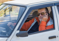 Retrato de un viejo hombre que se sienta en un coche viejo Fotos de archivo libres de regalías