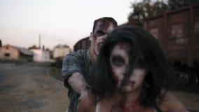 Retrato de un zombi femenino con la cara herida en el grito sangriento del vestido y del hombre del zombi detrás de ella que se a almacen de video