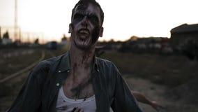 Retrato de un zombi masculino con los dientes sangrientos y el grito herido de la cara y de la muchacha del zombi detrás de él qu almacen de metraje de vídeo