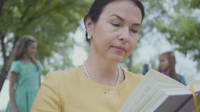 Retrato de una abuela mayor elegante que lee el libro en el parque en el primero plano Figuras borrosas de dos que juegan metrajes