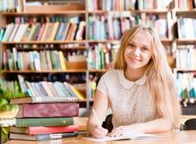 Retrato de una biblioteca de Girl Studying At del estudiante foto de archivo