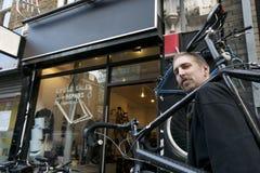 Retrato de una bicicleta que lleva del mediados de hombre adulto en hombro Foto de archivo libre de regalías