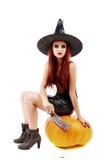 Retrato de una bruja pelirroja encantadora que sostiene la calabaza santifique Foto de archivo