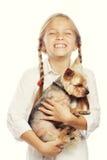 Retrato de una chica joven adorable que sonríe sosteniendo un perrito lindo Imagen de archivo libre de regalías