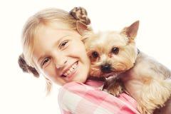 Retrato de una chica joven adorable que sonríe sosteniendo un perrito lindo Fotos de archivo libres de regalías