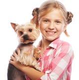 Retrato de una chica joven adorable que sonríe sosteniendo un perrito lindo Imagen de archivo