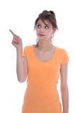 Retrato de una chica joven aislada ansiosa en la naranja que señala los wi Fotografía de archivo