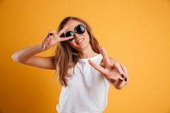 Retrato de una chica joven alegre en las gafas de sol que muestran paz Foto de archivo