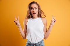Retrato de una chica joven alegre que muestra gesto de la paz Fotos de archivo libres de regalías