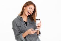 Retrato de una chica joven alegre que usa el teléfono móvil Foto de archivo libre de regalías