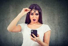 Retrato de una chica joven chocada que mira el teléfono móvil foto de archivo libre de regalías