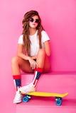 Retrato de una chica joven con el monopatín Foto de archivo