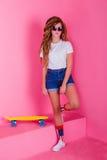 Retrato de una chica joven con el monopatín Fotos de archivo