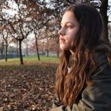 Retrato de una chica joven con el pelo largo, sentándose en el parque, mirando fijamente lejos soñando despierto fotos de archivo