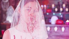 Retrato de una chica joven con un velo sangriento de la novia en su cara como traje de Halloween metrajes