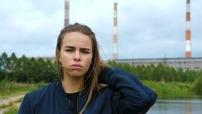 Retrato de una chica joven contra una planta hidroeléctrica almacen de video