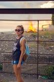 Retrato de una chica joven durante puesta del sol Gafas En el fondo quema el fuego Imagen de archivo