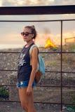 Retrato de una chica joven durante puesta del sol Gafas En el fondo quema el fuego Fotos de archivo