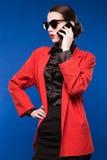 Retrato de una chica joven en gafas de sol y con un teléfono en su mano Fotos de archivo libres de regalías