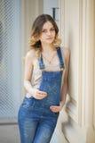 Retrato de una chica joven en guardapolvos del dril de algodón Imagenes de archivo