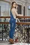 Retrato de una chica joven en guardapolvos del dril de algodón Imágenes de archivo libres de regalías