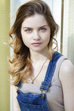 Retrato de una chica joven en guardapolvos del dril de algodón Foto de archivo libre de regalías