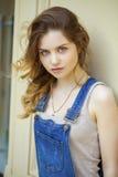 Retrato de una chica joven en guardapolvos del dril de algodón Foto de archivo