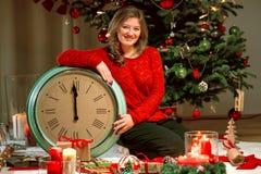 Retrato de una chica joven en suéter rojo con el reloj en el fondo de las luces de la Navidad imagen de archivo libre de regalías
