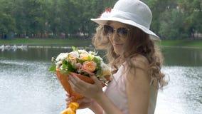 Retrato de una chica joven en un sombrero blanco con un ramo de flores almacen de video