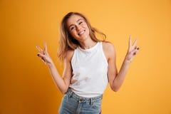 Retrato de una chica joven feliz que muestra gesto de la paz Foto de archivo libre de regalías