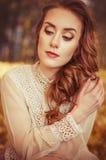 Retrato de una chica joven hermosa con los ojos azules, un vestido apacible del melocotón en un fondo de las hojas de otoño Foto de archivo libre de regalías