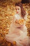 Retrato de una chica joven hermosa con los ojos azules y el pelo trenzado y un ramo de hojas de otoño en las manos, dres largos a Foto de archivo