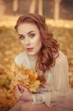 Retrato de una chica joven hermosa con los ojos azules y el pelo trenzado y un ramo de hojas de otoño en las manos, dres largos a Fotos de archivo libres de regalías