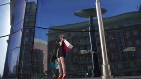 Retrato de una chica joven hermosa con los panieres en el fondo del escaparate blonde en el vestido negro, rojo almacen de metraje de vídeo