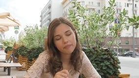 Retrato de una chica joven hermosa, ella está comiendo el helado en un café de la calle metrajes