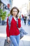 Retrato de una chica joven hermosa en camisa roja en el backgroun Foto de archivo libre de regalías