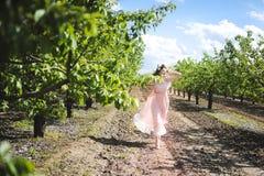 Retrato de una chica joven hermosa en un vestido del rosa de la oferta de la novia del vuelo en un fondo del campo verde, ella rí Fotos de archivo libres de regalías