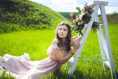 Retrato de una chica joven hermosa en un vestido del rosa de la oferta de la novia del vuelo en un fondo del campo verde, ella rí Foto de archivo