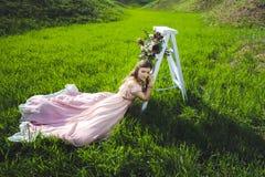 Retrato de una chica joven hermosa en un vestido del rosa de la oferta de la novia del vuelo en un fondo del campo verde, ella rí Fotografía de archivo libre de regalías