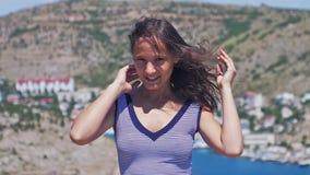 Retrato de una chica joven hermosa encima de la montaña con el aleteo alegre en el viento, sonrisa del pelo de la opinión del mar almacen de video
