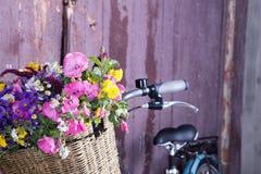 Retrato de una chica joven hermosa feliz con la bicicleta y las flores del vintage en fondo de la ciudad en la luz del sol al air Foto de archivo libre de regalías