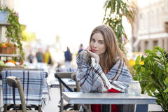 Retrato de una chica joven hermosa que se sienta en un café en el stre Foto de archivo libre de regalías