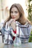 Retrato de una chica joven hermosa que se sienta en un café en el stre Imagenes de archivo