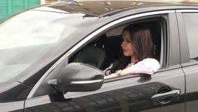 Retrato de una chica joven que conduce un coche moderno almacen de metraje de vídeo