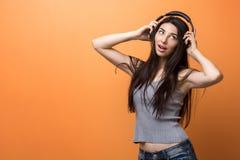 Retrato de una chica joven que escucha la música a través de los auriculares y que lo sostiene en sus manos contra fondo anaranja Imagen de archivo