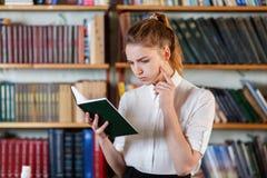 Retrato de una chica joven que está leyendo un libro en la biblioteca Foto de archivo