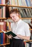 Retrato de una chica joven que está leyendo un libro en la biblioteca Fotos de archivo libres de regalías
