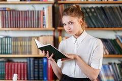 Retrato de una chica joven que está leyendo un libro en la biblioteca Imagen de archivo libre de regalías