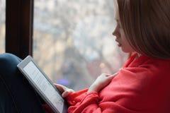 Retrato de una chica joven que lee un eBook en la ventana Imagen de archivo libre de regalías